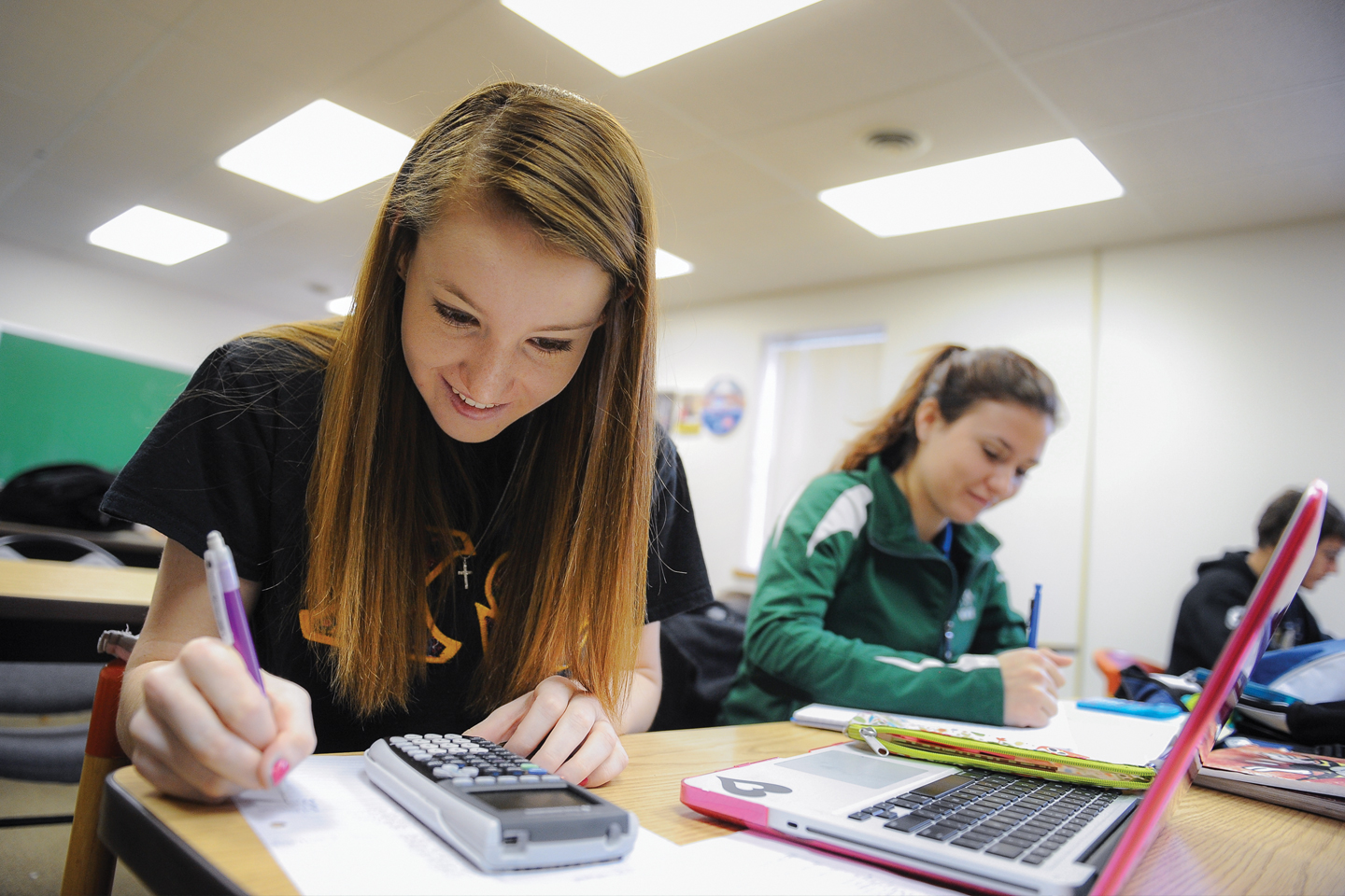 Image of smiling students working in class.