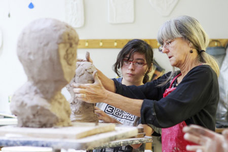 Female student works with Professor Jane Mudd on a sculpture.