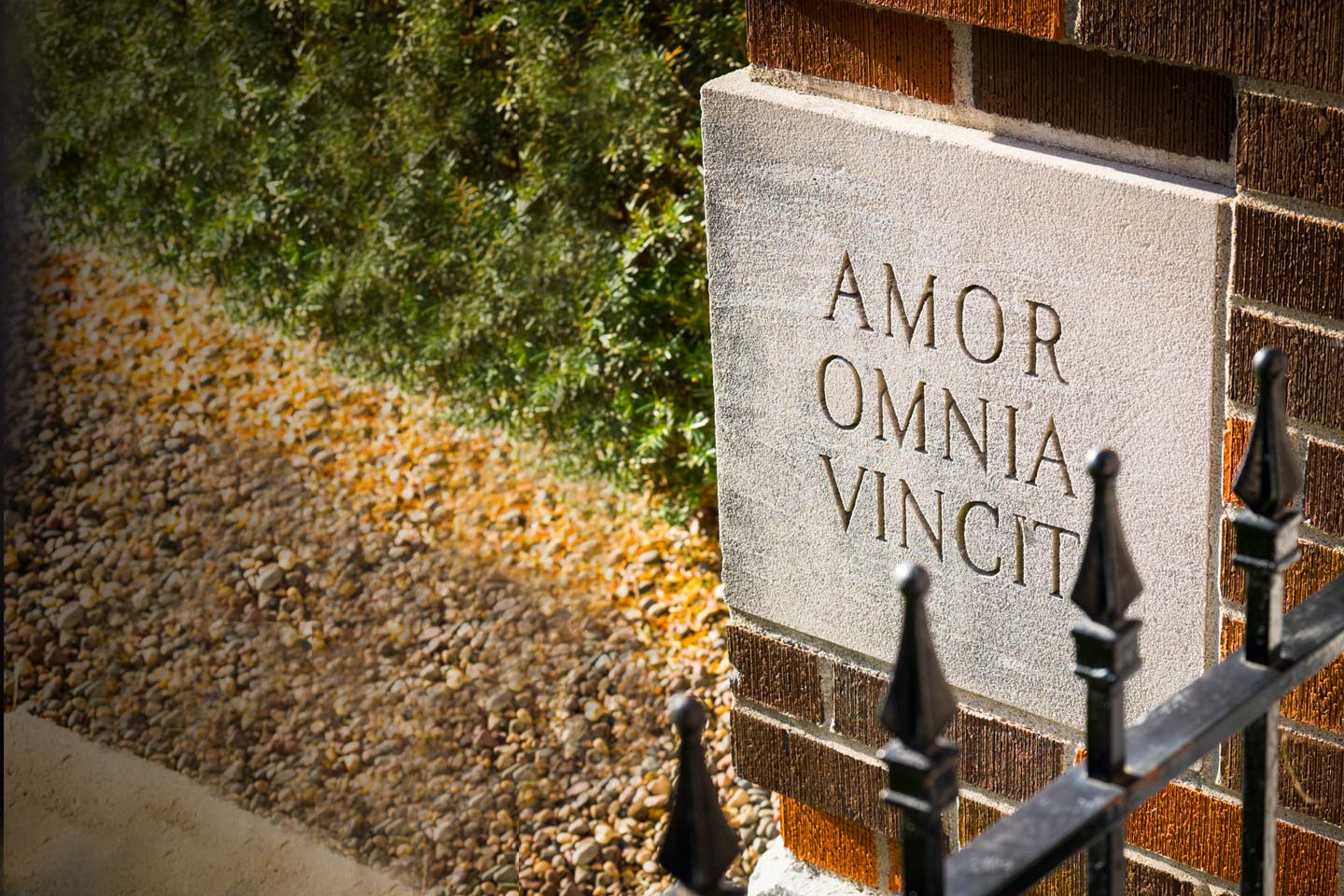 Shows cornerstone reading Amor Omnia Vincit - or Love Conquers All.