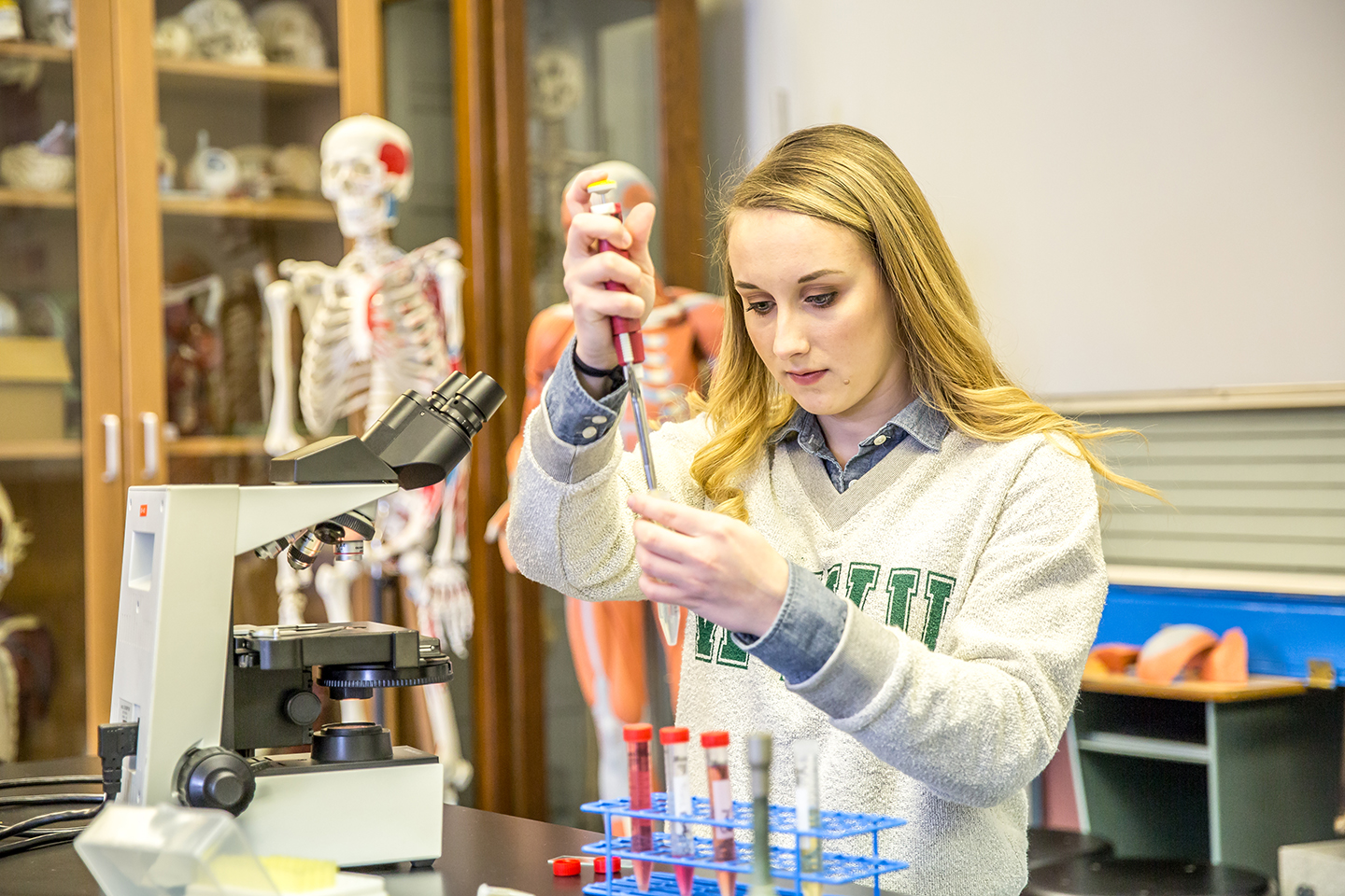 Biology student Ari Arnold working in a laboratory.