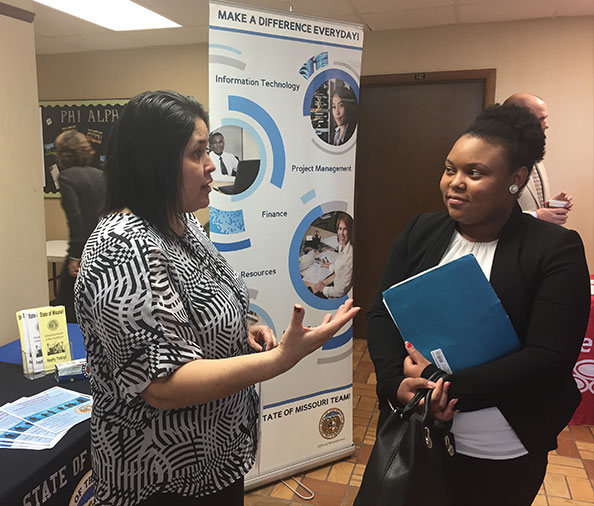 Image of a student visiting a booth at a career fair