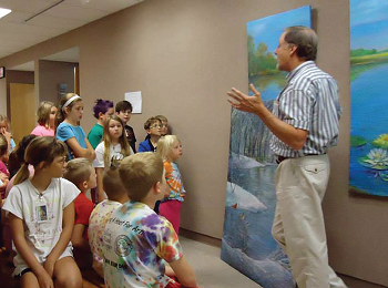 Prof. Terry Martin presents an art exhibit with a group of children in the halls of the Gladys Woods Kemper Center for the Arts.